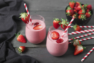 Glasses of strawberry smoothie and strawberries on dark wood - RTBF01200