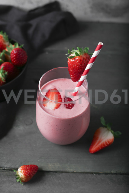 Glasses of strawberry smoothie and strawberries on dark wood - RTBF01206