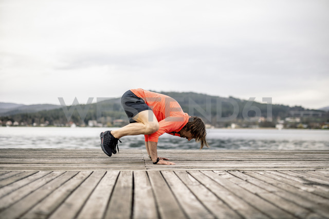 Athlete exercising on wooden deck at the lakeshore - DAWF00657