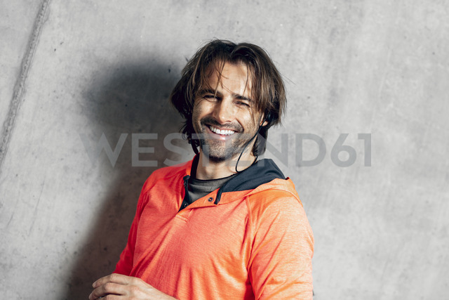 Portrait of smiling athlete at concrete wall - DAWF00660