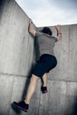 Athlete climbing up concrete wall outdoors - DAWF00666
