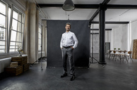 Portrait of mature businessman in front of black backdrop in loft - PDF01563