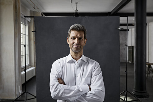 Portrait of mature businessman in front of black backdrop in loft - PDF01566