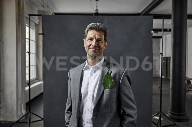 Portrait of mature businessman with leaf in pocket in front of black backdrop in loft - PDF01569
