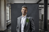 Portrait of mature businessman with leaf in pocket in front of black backdrop in loft - PDF01569