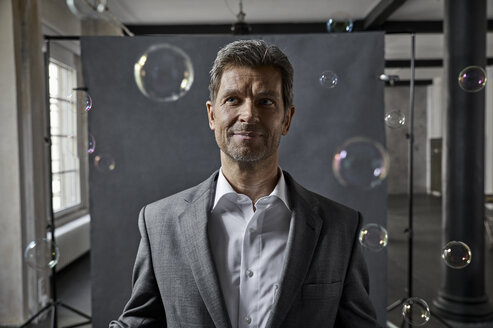 Portrait of mature businessman with bubbles in front of black backdrop in loft - PDF01572