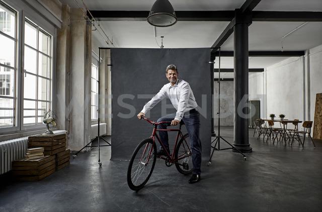 Portrait of mature businessman on fixie bike in front of black backdrop in loft - PDF01575