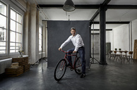 Portrait of mature businessman on fixie bike in front of black backdrop in loft - PDF01575