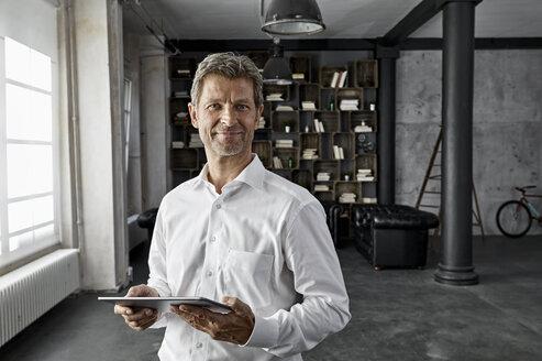 Portrait of mature man using digital tablet in loft flat - PDF01581