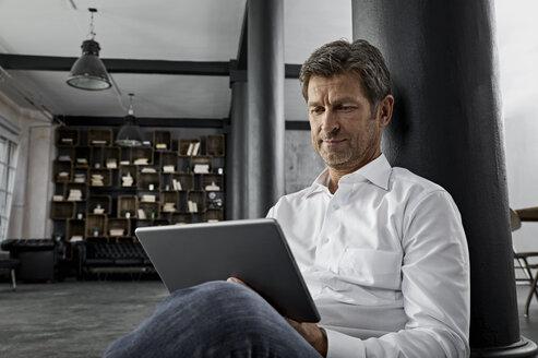Mature man sitting on the floor using digital tablet in loft flat - PDF01584
