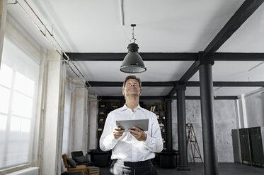 Mature man using digital tablet in loft flat - PDF01590
