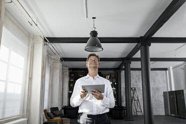 Mature man using digital tablet in loft flat - PDF01590