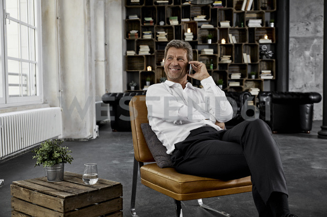 Smiling mature man using smartphone in loft - PDF01599