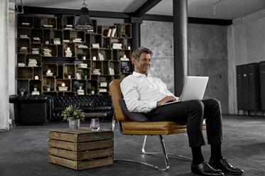 Smiling mature man using laptop in loft - PDF01602