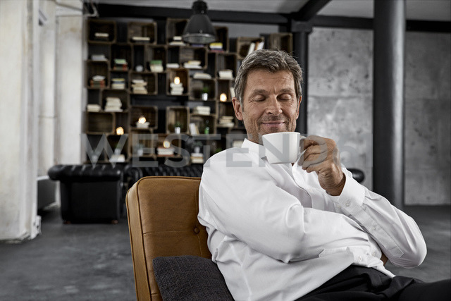 Portrait of mature man enjoying cup of coffee in loft - PDF01605