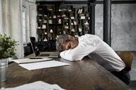 Mature businessman sleeping on desk in loft - PDF01614