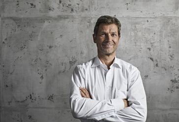Portrait of smiling mature man in front of concrete wall - PDF01617