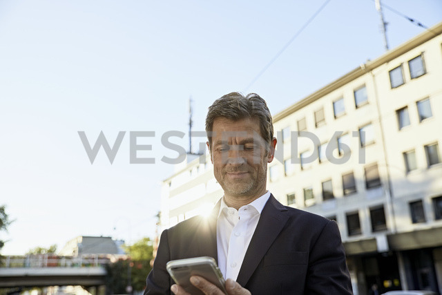 Mmature businessman using smartphone in the city - PDF01620
