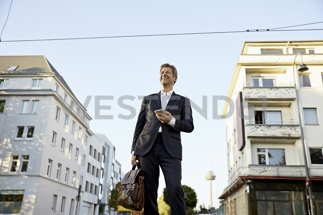 Happy mature businessman holding smartphone in the city - PDF01623