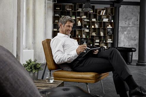 Mature man using digital tablet with digital pen in loft - PDF01626