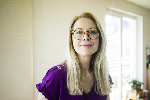 Portrait of smiling blond mature woman wearing glasses - MOEF01041
