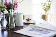 Newspaper, flower vases, loudspeaker and muffin on table - MOEF01044