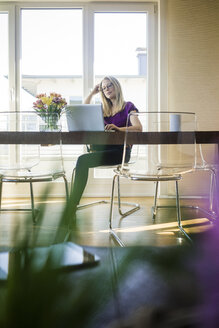 Businesswoman sitting at meeting table looking at laptop - MOEF01050