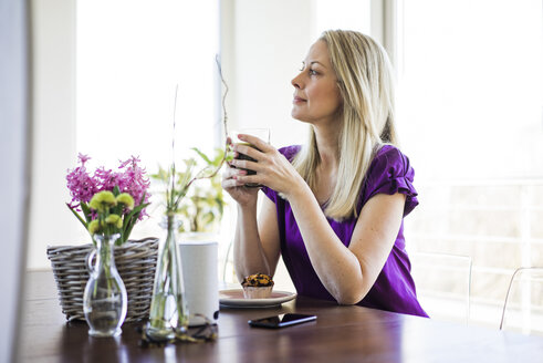 Mature woman sitting at table relaxing with glass of coffee - MOEF01053