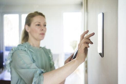Woman adjusting digital tablet mounted on wall with smartphone - MOEF01056
