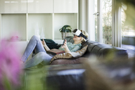 Woman lying on the couch with photo album using Virtual Reality Glasses - MOEF01059