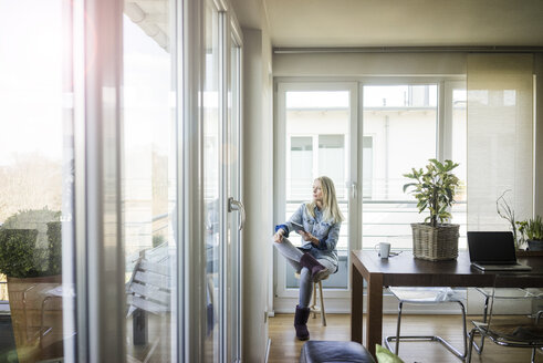 Woman with tablet sitting on stool looking out of window - MOEF01068