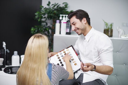 Woman choosing hair color from palette in hair salon - ABIF00340