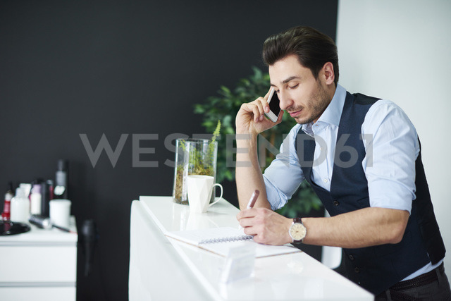 Hairdresser talking on cell phone checking diary - ABIF00358