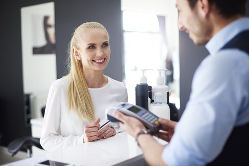 Woman paying at hair salon - ABIF00361