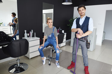 Portrait of confident hairdresser and woman in hair salon - ABIF00364