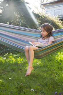 Little girl sitting on hammock in the garden reading a book - LVF06902