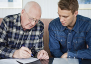 Man helping senior to fill in a form - MASF07035