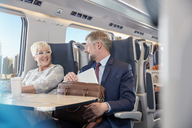 Businessman and businesswoman working, talking on passenger train - CAIF20237