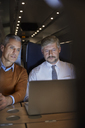 Businessmen working at laptop on passenger train at night - CAIF20255