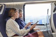 Businessman and businesswoman working, using digital tablet on passenger train - CAIF20258