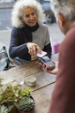 Woman using smart phone contactless payment at cafe - CAIF20267