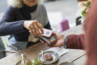 Woman with smart phone using contactless payment at cafe - CAIF20270