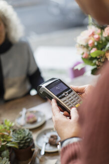 Cashier with credit card reader in cafe - CAIF20279