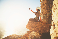Female rock climber with camera phone photographing sunny ocean view - CAIF20282