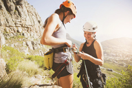 Female rock climbers preparing equipment - CAIF20291