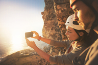 Rock climbers with camera phone photographing ocean view - CAIF20297