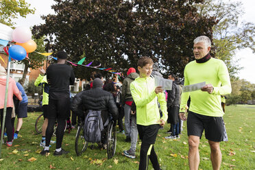 Father and son holding marathon bibs at charity run in park - CAIF20306