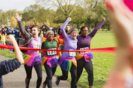 Enthusiastic female runners in tutus crossing charity run finish line in park, celebrating - CAIF20309