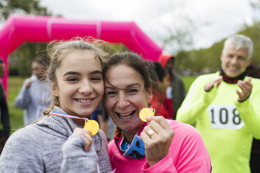 Portrait smiling, confident mother and daughter runners showing medals at charity run - CAIF20315
