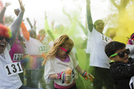 Playful crowd of runners throwing holi powder at charity run - CAIF20318